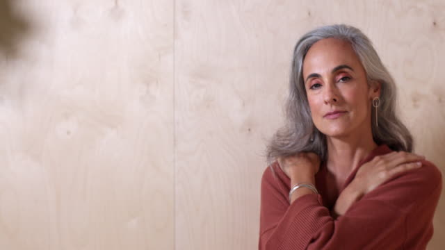 A middle-aged woman with gray hair places arms over chest as she turns toward camera and smiles, against a wooden wall background.