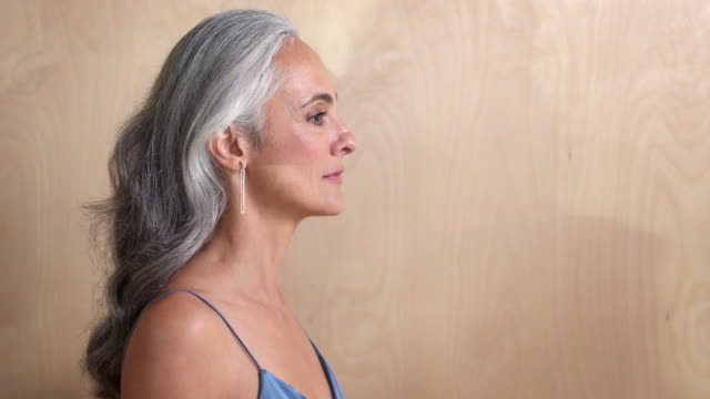 A middle-aged woman with gray hair turns toward camera and smiles, against a wooden wall background.