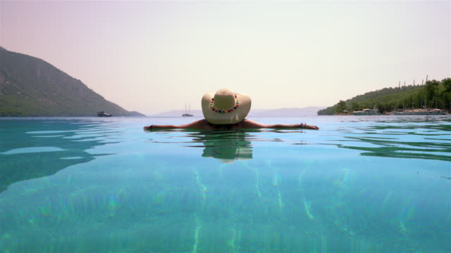 Middle-aged woman with hat, relaxes in the sea. Marmaris Turkey