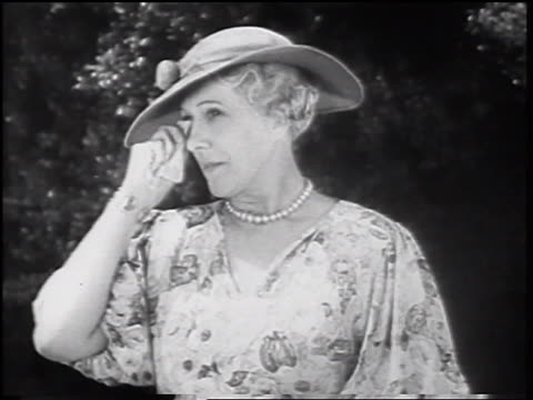 b/w 1935 middle-aged woman with pearls + hat looking offscreen + wiping eyes with tissue - 1935 stock videos & royalty-free footage