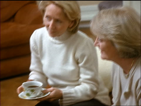 PAN 3 middle-aged women holding coffee cups sitting in living room talking + laughing