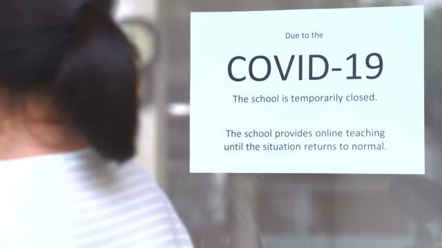 middle-aged women put the sign on the front door. to inform you that the school will change its teaching system to online due to the impact of the covid-19 epidemic. - banner sign stock videos & royalty-free footage