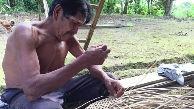 Middle-aged-Kichwa-Indian weaves basket in traditional manner of indigenous inhabitants of autonomous region of Sarayaku in Ecuadorian Amazon