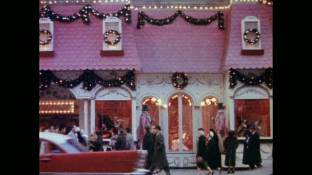 middleclass men and women walking past christmas store / cars and people reflected in the window glass / women coming out of revolving door / people... - 1958年点の映像素材/bロール