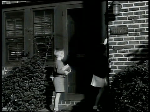 Middleclass residential street two children hugging woman at door walking into home Family of four in living room father sitting on floor w/ boy...