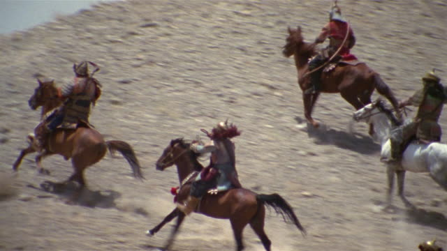 ms, pan, reenactment middle-eastern knights horseback riding in mountain landscape, middle ages style, iran  - the crusades stock videos & royalty-free footage