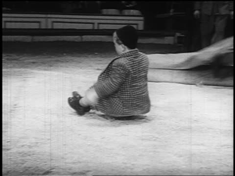 b/w 1955 pan midget clown bouncing on buttocks across floor / stands up + removes hat / circus - circus stock videos & royalty-free footage