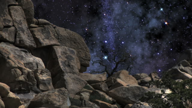 a midnight starry sky turns above giant rock formations. - digital enhancement stock videos and b-roll footage