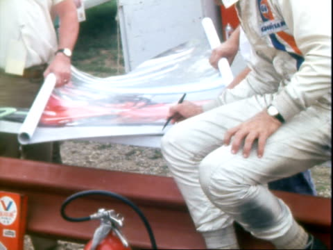 midohio road race course sign with illustrations of canam continental and transam class race cars at midohio sports car course / mechanics working on... - jumpsuit stock videos and b-roll footage
