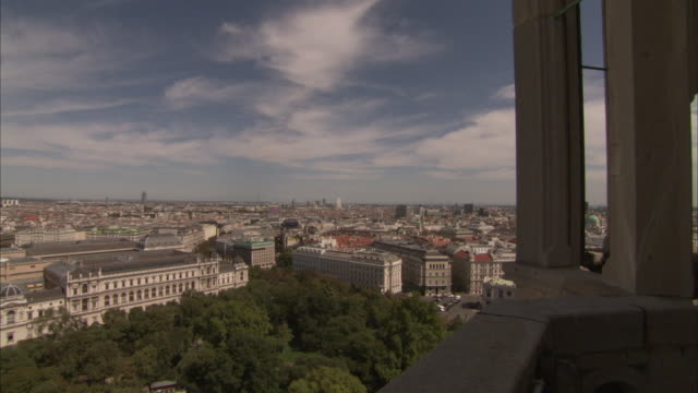 mid-rise apartment buildings stretch to the horizon beyond the spire of a cathedral in vienna. - spire stock videos & royalty-free footage