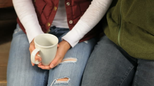 midsection handheld shot of woman holding coffee mug while sitting with man outdoors - jeans stock videos & royalty-free footage