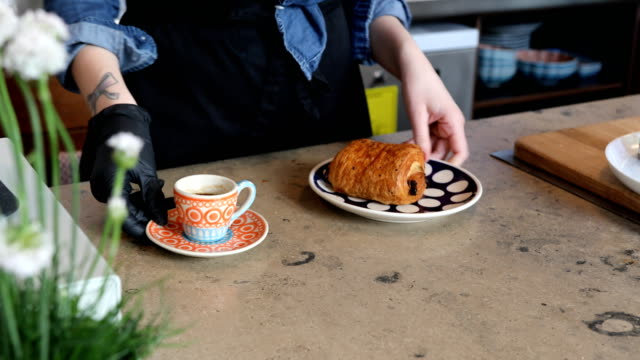 mittelteil des barista ist kaffee und brot servieren. - handschuh stock-videos und b-roll-filmmaterial
