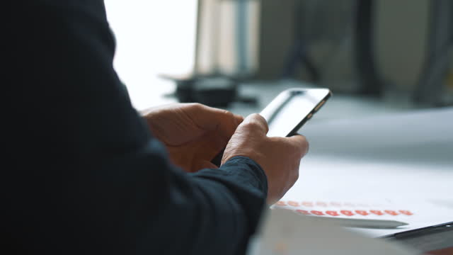 midsection of businessman texting through smart phone in new office - mittlerer teil stock-videos und b-roll-filmmaterial