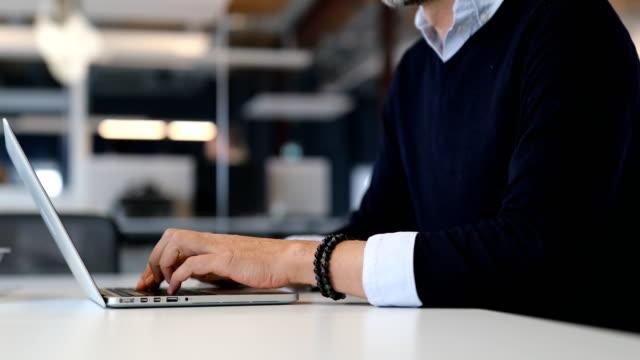 sezione centrale dell'uomo d'affari che usa laptop a tavola - only mature men video stock e b–roll