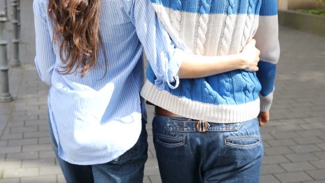 Midsection Of Couple Walking With Arm Around