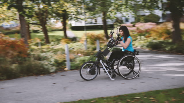 stockvideo's en b-roll-footage met midsection of disabled woman riding handcycle on road at park - rijwiel