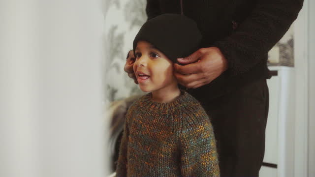 vídeos de stock, filmes e b-roll de midsection of father putting knit hat on his son at home - suéter