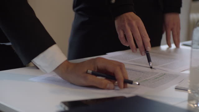 midsection of legal professionals discussing over document at table in law firm - law stock videos & royalty-free footage