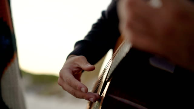 midsection of man playing guitar at beach - string instrument stock videos & royalty-free footage