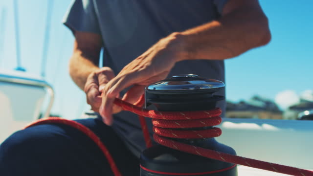 Midsection of man spooling rope on cleat in yacht