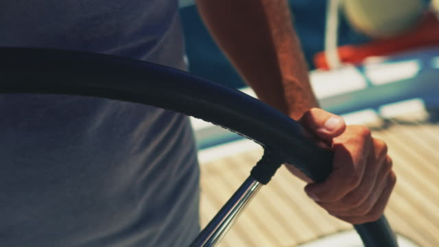 midsection of man steering yacht in summer - steering wheel stock videos & royalty-free footage