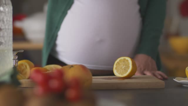 midsection of pregnant woman pouring a freshly squeezed lemon juice in a glass pitcher - pitcher jug stock videos & royalty-free footage