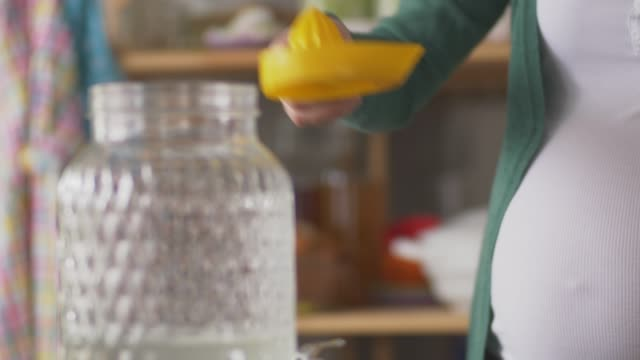 midsection of pregnant woman squeezing and pouring fresh lemon juice into glass pitcher - pitcher jug stock videos & royalty-free footage