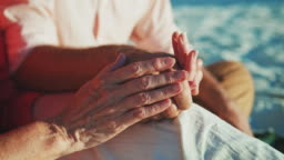 Midsection of senior couple holding hands at beach