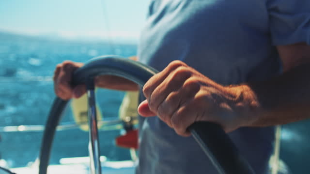 midsection of senior man steering yacht in summer - helm stock videos & royalty-free footage