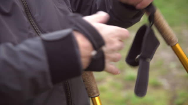 midsection of senior man wearing nordic walking pole in hands while standing on field - wanderstock stock-videos und b-roll-filmmaterial