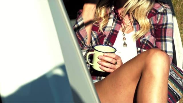 vídeos de stock e filmes b-roll de midsection of woman having coffee in van trunk - camping
