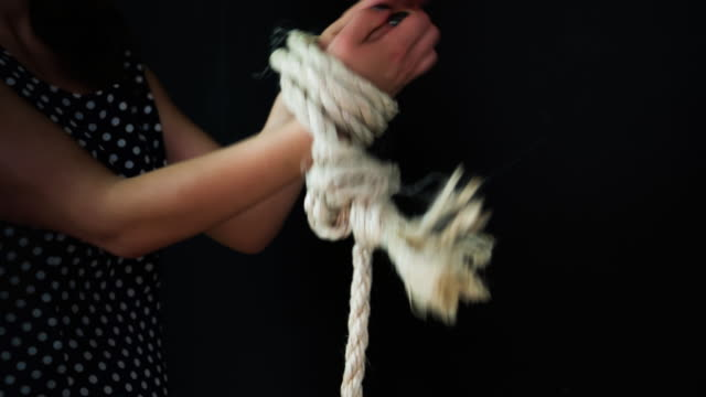vídeos de stock e filmes b-roll de midsection of woman tied up with rope - fundo preto