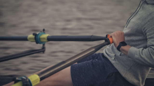 midsection of young man rowing boat in river - sculling stock videos & royalty-free footage
