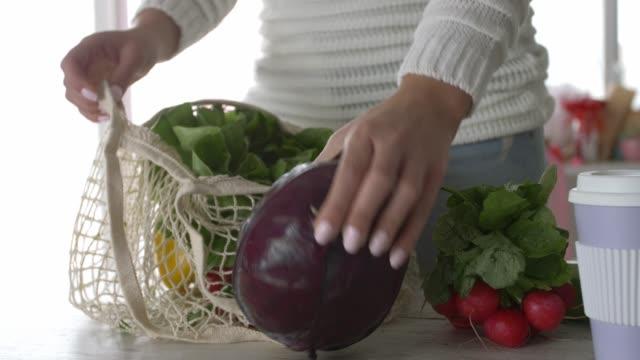 vidéos et rushes de section médiane de la jeune femme déballant des légumes du sac à provisions durable - tasse