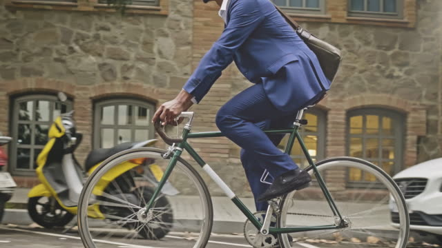 vídeos de stock e filmes b-roll de mid-section slow motion video of businessman riding a  bicycle in the city - transportation