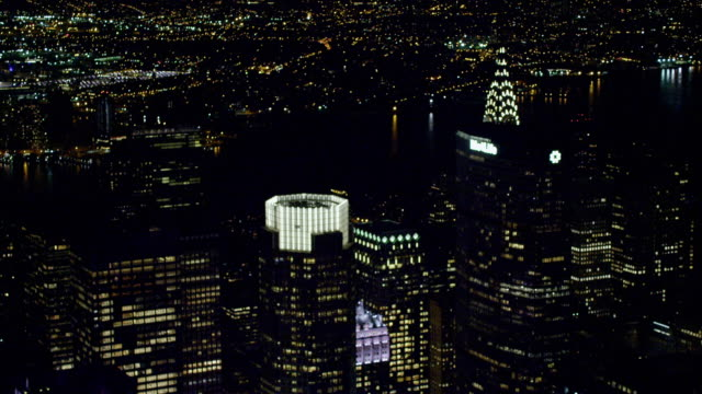 ws midtown chrysler building art deco terraced lighted top crown w/ flood lights below moving backward south passing metlife building to ge building... - metlife hochhaus stock-videos und b-roll-filmmaterial
