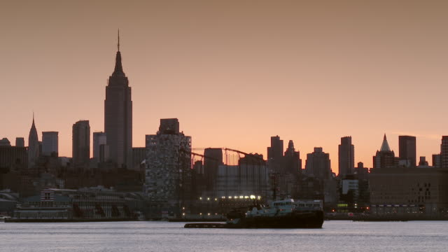A midtown early morning skyline featuring Chelsea Piers and The Empire States Building.  A tug boat crosses the frame pulling a barge.