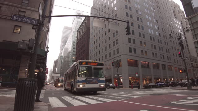 midtown intersection of madison avenue and 45th street traffic during the coronavirus pandemic with yellow taxi cab, the m4 bus, an american usa flag... - yellow taxi stock videos & royalty-free footage