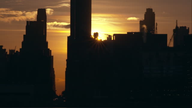 Midtown Manhattan at sunrise.  The sun peeks over the water towers.