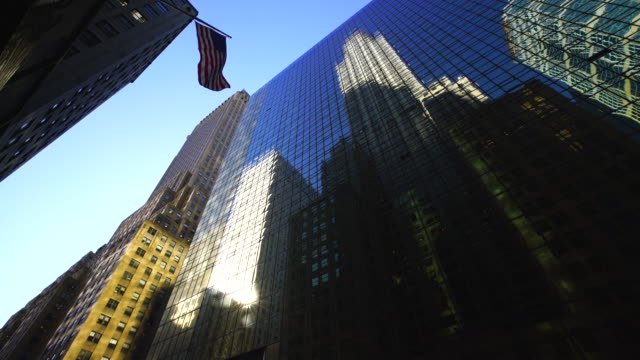 Midtown Manhattan buildings reflect to the building surface at front in New York. An American Flag shaking by winds.