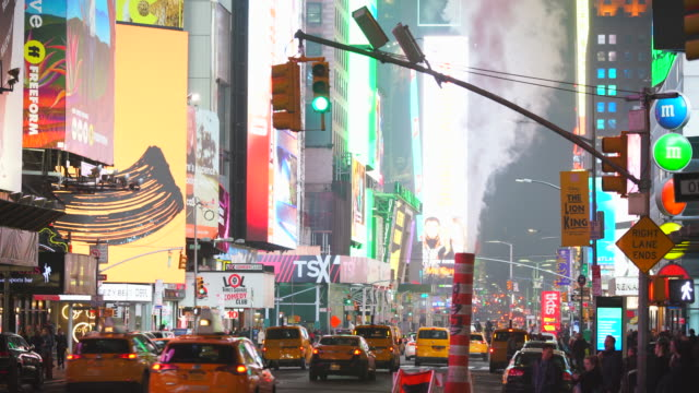 midtown manhattan heavy traffic goes through and a crowd of people crosses on the avenue under the drifting steam in the night around the times square in midtown manhattan new york city ny usa on jan. 14 2020. - nordamerika stock-videos und b-roll-filmmaterial