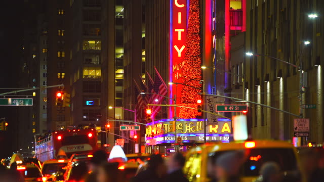 midtown manhattan heavy traffic move on the sixth avenue and people cross the avenue under the radio city music hall glowing christmas tree in the night at new york city ny usa on jan. 02 2020. - radio city music hall stock videos & royalty-free footage