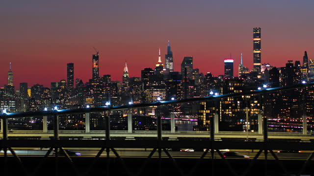 midtown manhattan illuminated skyline in the night. the view over rfk bridge with traffic on it. drone footage with the panning camera motion. - panning stock videos & royalty-free footage