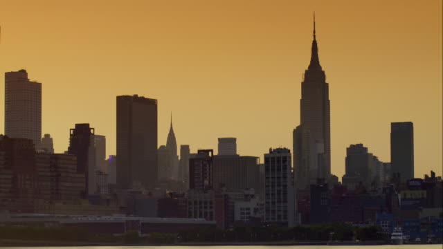 Midtown Manhattan skyline against an orange sky at dawn along the Hudson River.