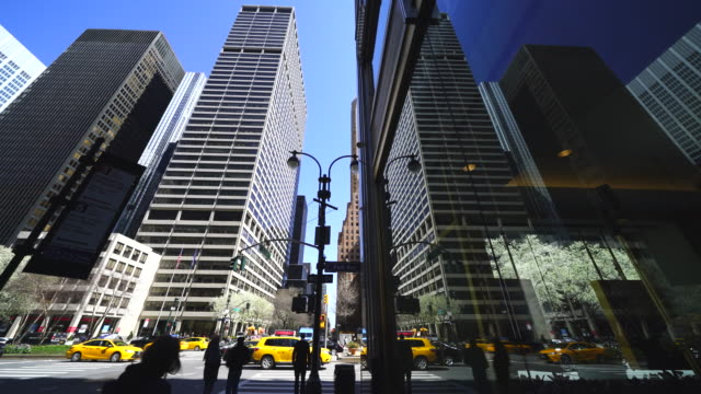 stockvideo's en b-roll-footage met midtown manhattan skyscrapers, traffic and people reflect to building window at new york ny usa on apr. 21 2018. - gele taxi