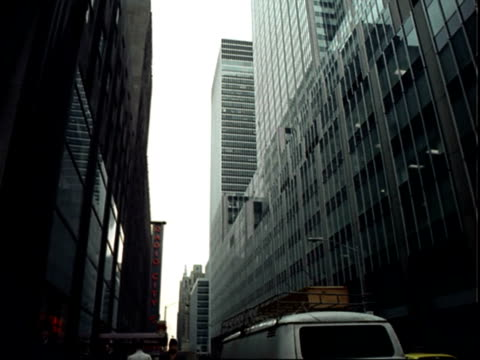 midtown manhattan 'stop' and 'one way' signs flanked by tall office buildings pan slowly left to more buildings including rockefeller center /... - radio city music hall stock videos & royalty-free footage