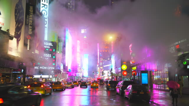 midtown manhattan traffic goes through the avenue under the drifting steam in the rainy night around the times square in midtown manhattan new york city ny usa on feb. 25 2020. - billboard stock videos & royalty-free footage