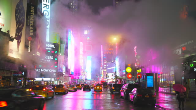midtown manhattan traffic goes through the avenue under the drifting steam in the rainy night around the times square in midtown manhattan new york city ny usa on feb. 25 2020. - reklamskylt bildbanksvideor och videomaterial från bakom kulisserna