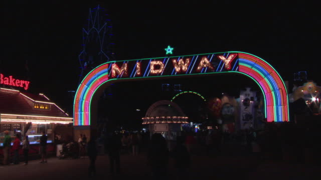 ws midway neon sign in amusement park at night, dallas, texas, usa - fahrkartenschalter stock-videos und b-roll-filmmaterial