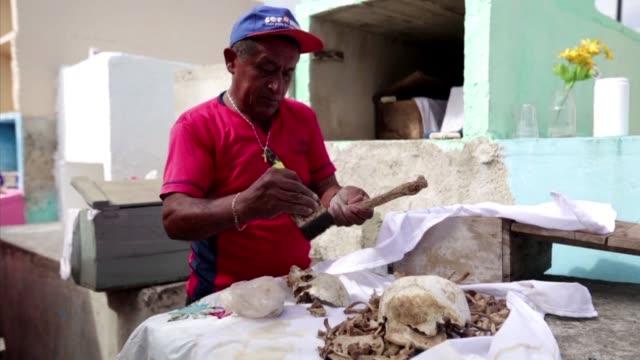 miembros de una pequena comunidad maya al sur de mexico limpian los esqueletos de sus familiares fallecidos honrando el vinculo entre la vida y la... - día stock videos & royalty-free footage